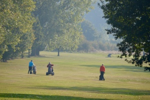 Golfers walk their caddies along the green of the 5th hole at Chingford Golf Course on a foggy morning