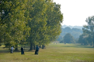 Golfers walk their caddies toward the 6th hole at Chingford Golf Course on a foggy morning